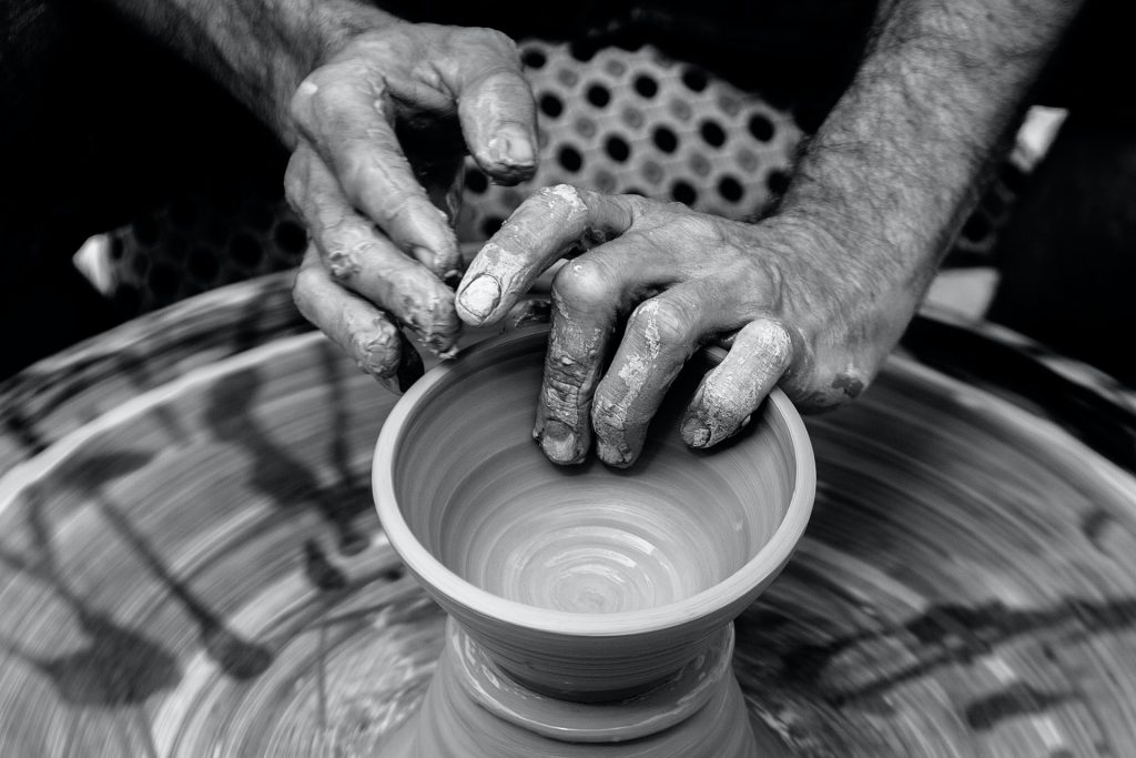 Hands forming a clay pot on a pottery wheel